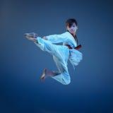 在蓝色背景的年轻男孩训练空手道 库存照片