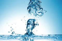 在蓝色背景的水飞溅 库存照片