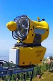 在蓝色背景的Snowmaking,在夏天 黄色雪大炮在喀尔巴阡山脉,罗马尼亚 库存图片