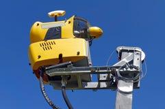 在蓝色背景的Snowmaking 黄色雪大炮在喀尔巴阡山脉,罗马尼亚 免版税库存图片