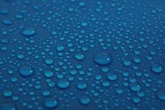在蓝色背景纹理的水下落 免版税库存照片