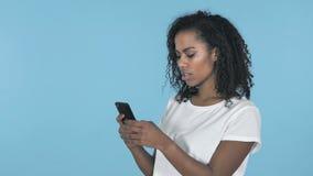 在蓝色背景隔绝的非洲女孩浏览智能手机 股票录像