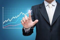 在蓝色背景隔绝的商人常设姿势手接触图表财务 免版税库存照片