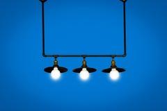 在蓝色背景隔绝的垂悬的电灯泡 免版税库存照片