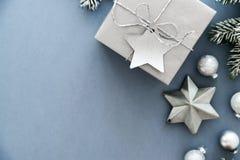 在蓝色背景顶视图的圣诞节银色手工制造礼物盒 圣诞快乐贺卡,框架 冬天xmas假日题材