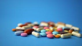 在蓝色背景驱散的极少数色的药片 股票视频