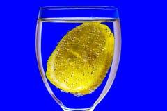 在蓝色背景,一块玻璃用用气体bubb盖的柠檬 库存照片