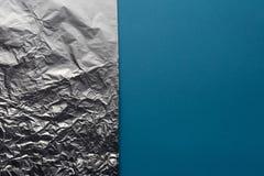 在蓝色背景,平的位置的纹理银色铝芯 免版税图库摄影