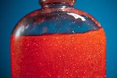 在蓝色背景,特写镜头视图的红色阵雨胶凝体 库存照片