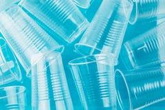 在蓝色背景,顶视图的新的干净的空的透明一次性塑料玻璃 免版税图库摄影