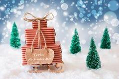 在蓝色背景, Frohe Weihnachten的雪橇意味圣诞快乐 免版税图库摄影