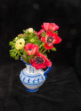 在蓝色花瓶的银莲花属 免版税库存照片