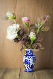 在蓝色花瓶静物画的美丽的花在木背景 图库摄影