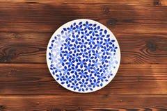 在蓝色花的被绘的板材在木背景 免版税库存照片