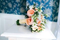 在蓝色葡萄酒墙壁附近的新娘花束在白色桌上 免版税图库摄影