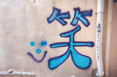 在蓝色街道画写的微笑的汉字在墙壁在香港 库存图片