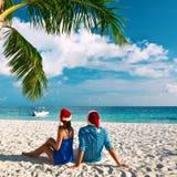 在蓝色衣裳的夫妇在圣诞节的一个海滩 免版税图库摄影
