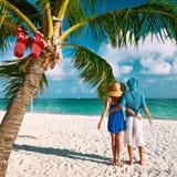 在蓝色衣裳的夫妇在圣诞节的一个海滩 免版税库存照片