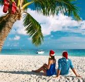 在蓝色衣裳的夫妇在圣诞节的一个海滩 图库摄影