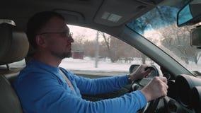 在蓝色衬衣和玻璃的白色司机驾驶沿多雪的城市的汽车在晴朗的下午 o 股票视频