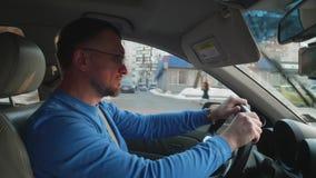 在蓝色衬衣推进汽车保护的眼睛的白色司机从与汽车遮阳增量剂的太阳 Sunnny下午在冬天 影视素材