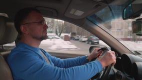 在蓝色衬衣推进汽车的白色司机在用雪和接近的遮阳帘增量剂盖的城市 股票视频