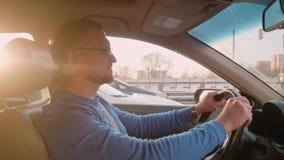 在蓝色衬衣的白色司机在堵车的汽车坐 美丽的背后照明 影视素材