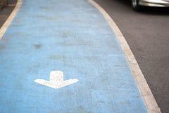 在蓝色路的白色箭头标志有线和运动汽车的在公园 库存图片