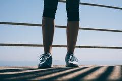 在蓝色运动鞋的苗条女性腿在早晨太阳 免版税库存照片