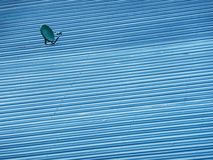 在蓝色金属板屋顶的小绿色卫星盘 库存图片