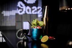 在蓝色钢杯子的新鲜的可口鸡尾酒用薄菏和红色莓果 免版税库存图片