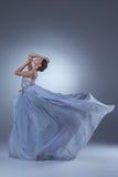 在蓝色长的礼服的美好的芭蕾舞女演员跳舞 免版税库存照片