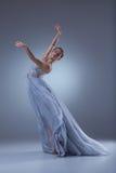 在蓝色长的礼服的美好的芭蕾舞女演员跳舞 免版税图库摄影