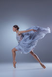 在蓝色长的礼服的美好的芭蕾舞女演员跳舞 免版税库存图片