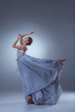 在蓝色长的礼服的美好的芭蕾舞女演员跳舞 图库摄影