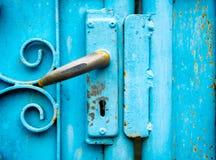 在蓝色门缝的关键锁老 免版税库存照片