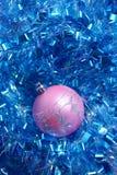 在蓝色闪亮金属片的桃红色圣诞节球 免版税库存图片
