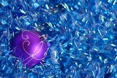 在蓝色闪亮金属片的紫罗兰色圣诞节球 库存照片