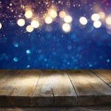 在蓝色闪烁前面的空的桌点燃背景 库存照片