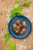 在蓝色陶瓷板材的半生半熟油煎的切成小方块的用卤汁泡的牛肉在与装饰的海盐和菜的木盘区 库存图片