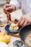 在蓝色陶瓷板材的厨师镀层油煎的扇贝 免版税图库摄影
