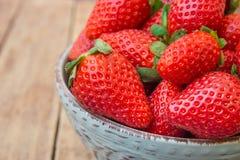 在蓝色陶瓷碗的成熟有机草莓在板条木背景,关闭,健康食物 图库摄影
