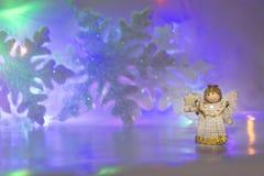 在蓝色雪花背景的木天使 免版税库存图片