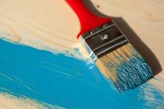 在蓝色颜色的红色刷子油漆木头 库存图片
