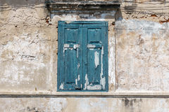 在蓝色颜色的老窗口在肮脏的墙壁上 库存图片