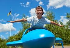 在蓝色飞机吸引力在公园,愉快的童年,暑假概念的儿童飞行 免版税库存照片