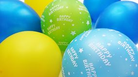 在蓝色黄色苹果绿的五颜六色的与生日快乐文本的气球和绿松石 免版税库存图片