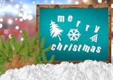 在蓝色黑板的圣诞快乐有blurr城市杉木和雪的 库存照片