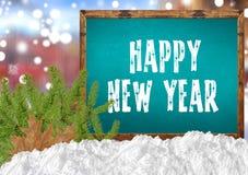 在蓝色黑板的新年快乐有blurr城市杉木和雪的 免版税库存图片