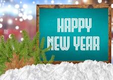 在蓝色黑板的新年快乐有blurr城市杉木和雪的 库存图片